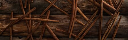 top view of cinnamon sticks scattered on wooden background, panoramic shot Stockfoto
