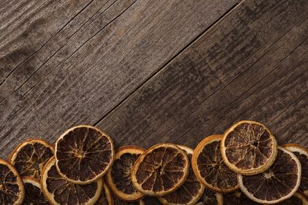 top view of dried orange slices on wooden background with copy space