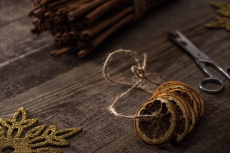 selective focus of dried citrus slices on thread near cinnamon, scissors and snowflake on wooden background Stockfoto