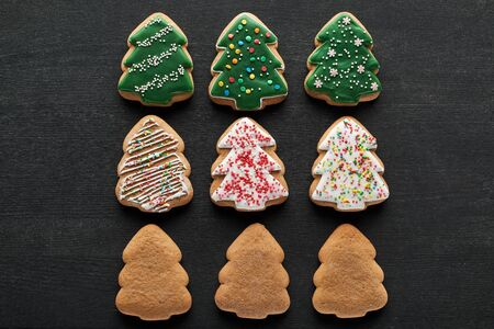 flat lay with delicious glazed Christmas tree cookies on black background