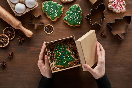 cropped view of woman closing gift box with Christmas tree cookie on wooden table