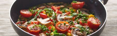 close up of delicious omelet with mushrooms, tomatoes and greens in frying pan