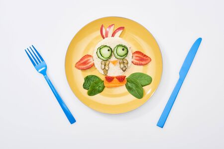 top view of plate with fancy cow made of food for childrens breakfast near cutlery on white background Stock fotó
