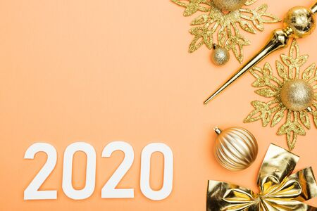 top view of white 2020 numbers near golden christmas decoration on orange background