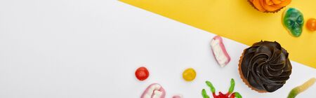 panoramic shot of colorful gummy sweets and cupcakes on yellow and white background, Halloween treat
