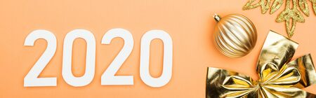 top view of white 2020 numbers near golden christmas decoration on orange background, panoramic shot