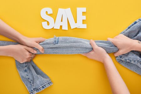 cropped view of women pulling jeans with sale lettering above on yellow background Reklamní fotografie