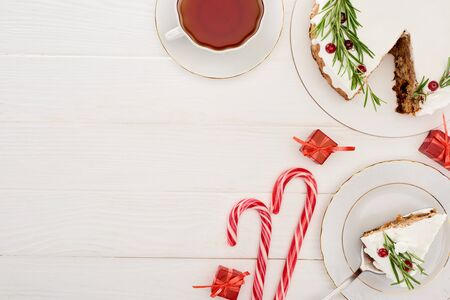 top view of christmas pie on white wooden table with cup of tea, candy canes and little gifts Banco de Imagens