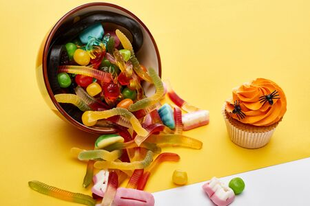 colorful gummy sweets scattered from bowl near cupcake on yellow background, Halloween treat