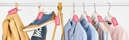 sneakers, accessories and elegant shirts hanging with sale labels isolated on white, panoramic shot