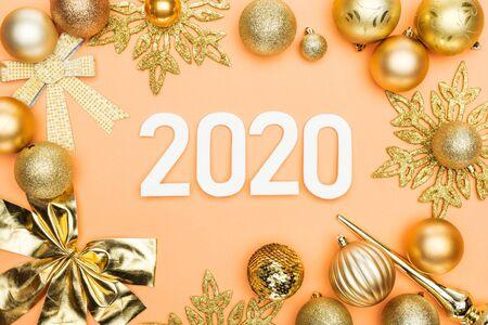 Blick von oben auf die weißen 2020-Nummern im Rahmen der goldenen Weihnachtsdekoration auf orangefarbenem Hintergrund Standard-Bild