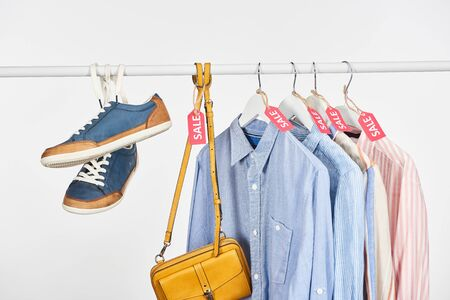 sneakers, bag and elegant shirts hanging with sale labels isolated on white Imagens
