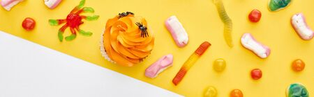 panoramic shot of colorful gummy sweets and cupcake on yellow and white background, Halloween treat