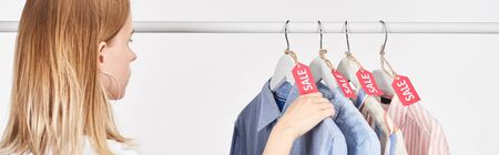 blonde woman near elegant shirts hanging with sale labels isolated on white, panoramic shot