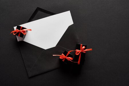 top view of black envelope with blank card near decorative gift boxes on black background