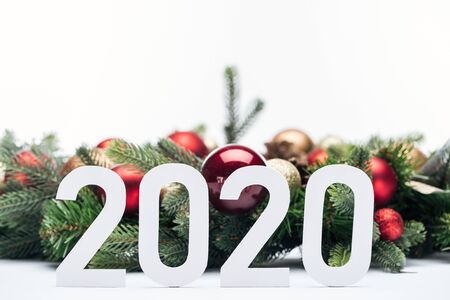 paper 2020 numbers near Christmas tree wreath with baubles isolated on white