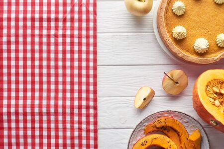 tasty pumpkin pie with whipped cream near checkered tablecloth, raw and baked pumpkins, whole and cut apples on white wooden table