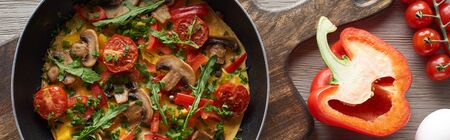 top view of homemade omelet in frying pan with bell pepper and cherry tomatoes on wooden board Banco de Imagens