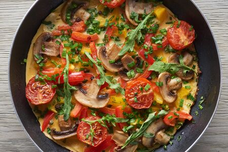 top view of omelet with mushrooms, tomatoes and greens in frying pan
