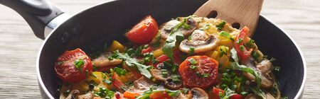 close up of homemade omelet with mushrooms, tomatoes and greens in frying pan with wooden shovel