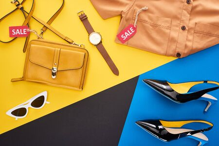 top view of clothes, shoes and accessories with sale labels on blue, yellow and black background