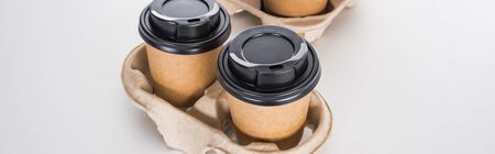 panoramic shot of paper cups with coffee in cardboard tray on white background 写真素材