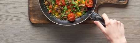 top view of woman cooking omelet with mushrooms, tomatoes and greens on frying pan