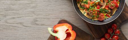 top view of omelet in frying pan on wooden board with bell pepper and tomatoes Stock fotó