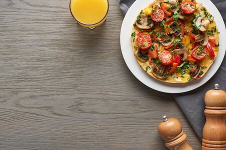 top view of glass of juice and tasty omelet with vegetables for breakfast on wooden table with pepper and salt
