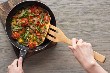 top view of woman cooking omelet with mushrooms, tomatoes and greens on frying pan with wooden shovel Stock fotó