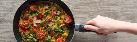 cropped view of woman cooking omelet with mushrooms, tomatoes and greens on frying pan Stock fotó