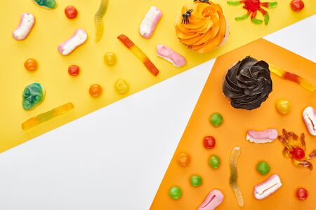 top view of colorful gummy sweets and cupcakes on yellow and white background, Halloween treat