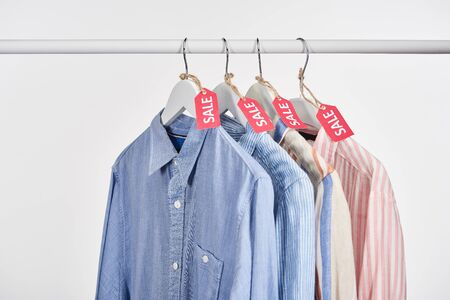 elegant shirts hanging with sale labels isolated on white