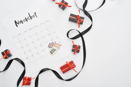 top view of calendar with November 29 marked date on white background with black ribbon and presents Banco de Imagens
