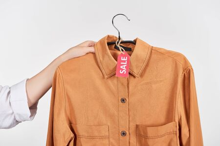 cropped view of woman holding hanger with shirt with sale label isolated on white