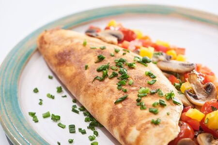 close up of homemade wrapped omelet with mushrooms, tomatoes, greens and peppers on plate