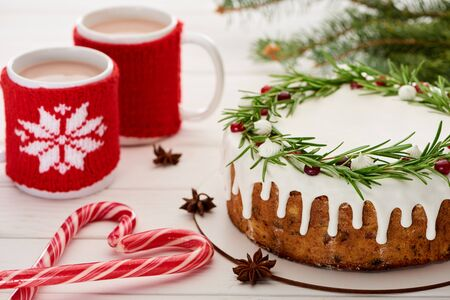 candy canes, christmas pie with icing and two cups of coffee on white wooden table