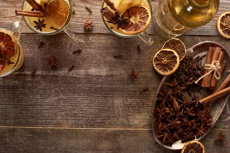 top view of traditional pear mulled wine with spices on wooden rustic table