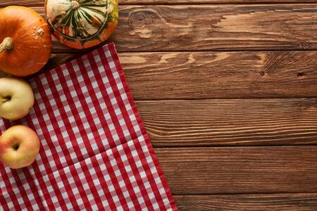 top view of checkered tablecloth with fresh apples and pumpkins on wooden surface with copy space Imagens