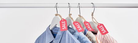 elegant shirts hanging with sale labels isolated on white, panoramic shot Stockfoto