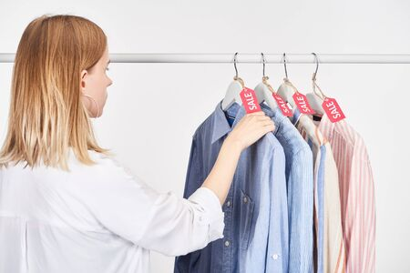blonde woman near elegant shirts hanging with sale labels isolated on white