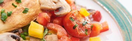 close up of yummy wrapped omelet with tomatoes and peppers on plate Stock Photo