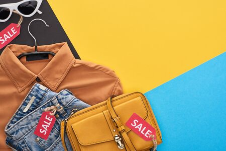 top view of clothes and accessories with sale labels on blue, yellow and black background