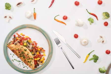 top view of plate with homemade wrapped omelet with vegetables on white table with ingredients, fork and knife
