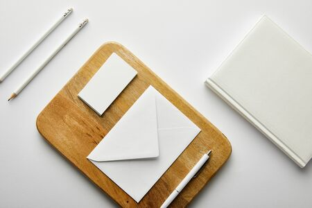 top view of envelope, business card and pen on wooden board, notebook, pencils