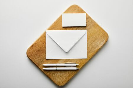 top view of envelope, business card and pens on wooden board