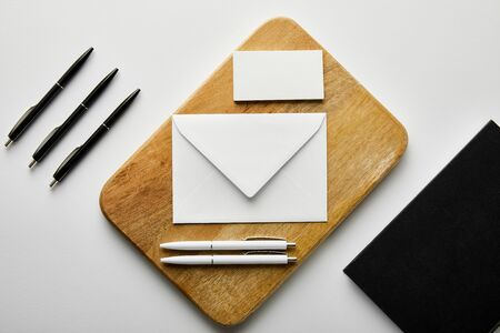 top view of envelope, business card and white pens on wooden board, notebook and black pens on table