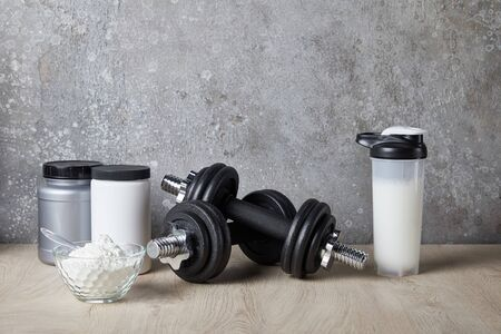 protein shake in sports bottle near jars near concrete wall Imagens