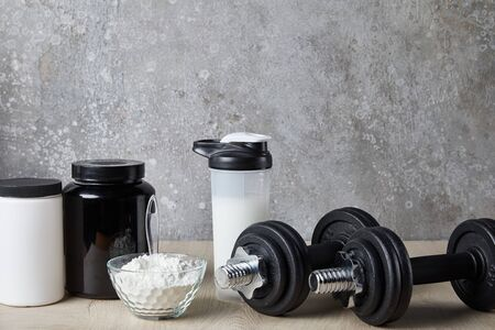 dumbbells near protein shake in sports bottle and protein powder near concrete wall