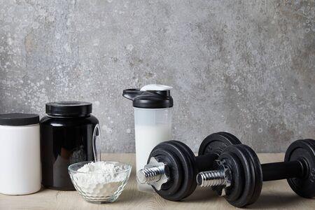 manubri vicino al frullato proteico in una bottiglia sportiva e polvere proteica vicino al muro di cemento